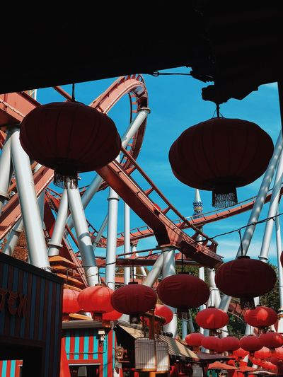 Low angle view of lanterns hanging against rollercoaster