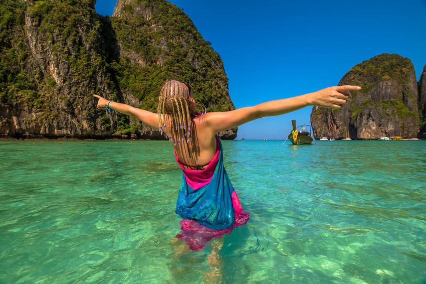Back of happy and fashionable tourist woman with colorful sarong in turquoise water of Maya Bay famous lagoon of The Beach movie, Phi Phi Leh, Andaman Sea in Thailand Fashionable and happy tourist with sarong and pink wide-brimmed hat making a selfie on tropical famous beach of Nai Harn Beach, Rawai, Phuket, Thailand. Happy tourist enjoys panorama from Sail Rock View Point of kor 8 of Similan Islands National Park, Phang Nga, Thailand, one of the tourist attraction of the Andaman Sea. Happy woman with bikini and shorts, jumping in the air on Ya Nui Beach, a little cove divided by a rocky cape, Phuket, Thailand, Asia. Happy Koh Rok Islands Nui Beach Phang Nga Bay Phuket Thailand Tanning ☀ Thailand Vacations Woman Beach Beauty In Nature Clear Sky Day Full Length Girl Happiness Koh Rok Leisure Activity Lifestyles Nature One Person Outdoors People Phang Nga Rawai Real People Rock - Object Scenics Sea Seascape Sky Surin Islands Travel Destinations Tree Vacations Water Young Adult
