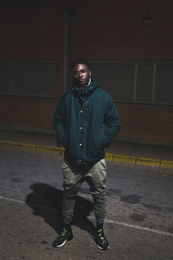 Portrait of young man standing against wall at night