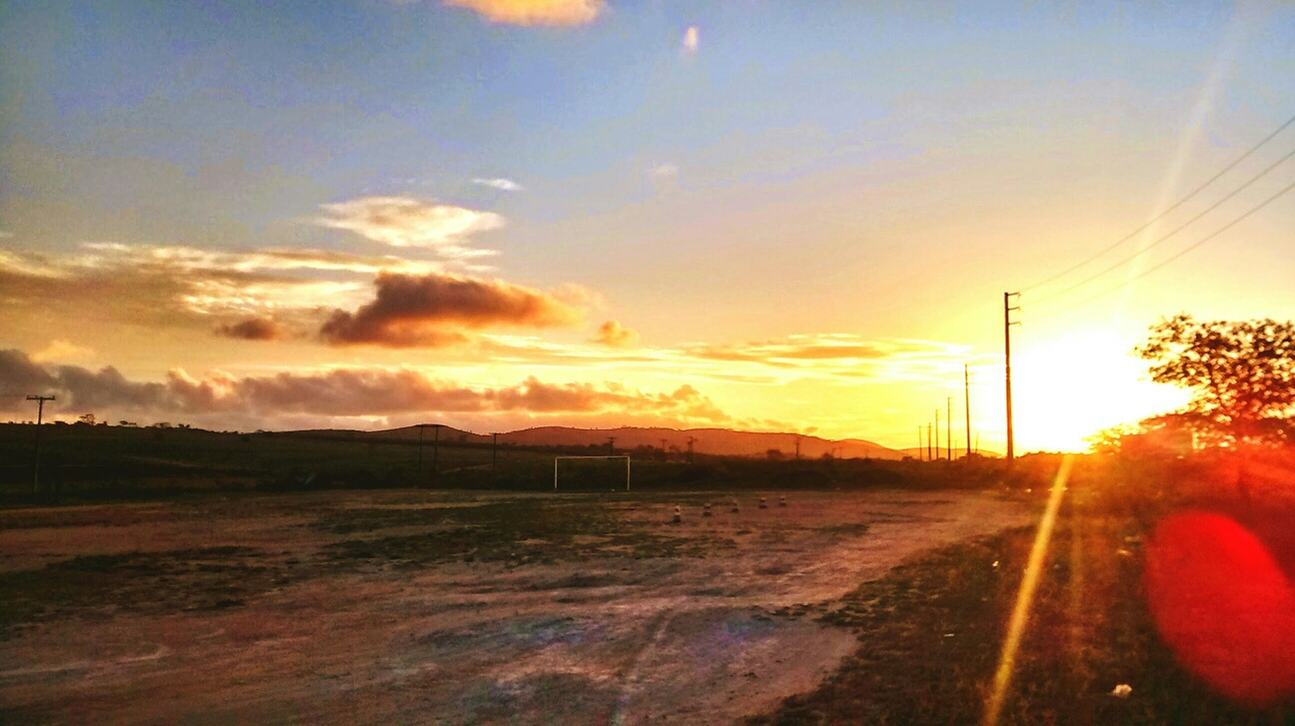 sunset, sun, sky, orange color, lens flare, sunbeam, sunlight, transportation, road, landscape, tranquil scene, scenics, tranquility, beauty in nature, nature, cloud - sky, field, idyllic, the way forward, outdoors