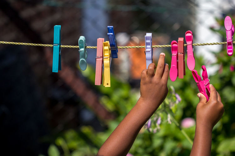 Close-Up Of Hand Holding Clothespins Hanging On Clothesline