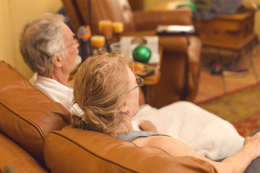 Older couple relaxing on a nice leather couch and watching television at home. Adult Gray Hair Indoors  Leisure Activity Lifestyles Men Real People Relaxation Retirement Senior Adult Senior Couple Senior Men Senior Women Short Hair This Is Aging Togetherness Two People Women