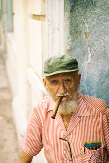 Portrait of senior man wearing cap smoking cigar while sitting outdoors