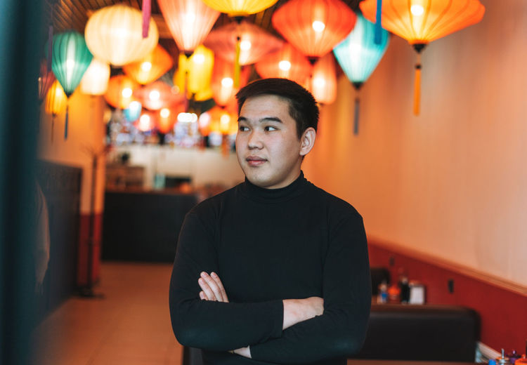 Portrait of young man standing against illuminated lights