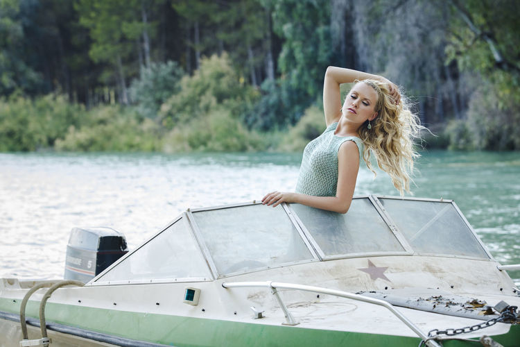 Attractive blond girl with curly hair and blue eyes wearing a short green summer dress on a small boat. Young woman portrait with a natural background Adult Beautiful Woman Blond Hair Day Hair Hairstyle Happiness Leisure Activity Mode Of Transportation Nature Nautical Vessel One Person Outdoors Portrait Smiling Transportation Travel Water Women Young Adult