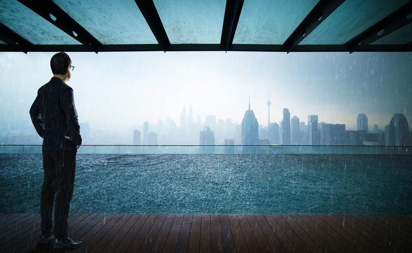Rear View Of Businessman Standing On Pier By River Against Cityscape During Monsoon