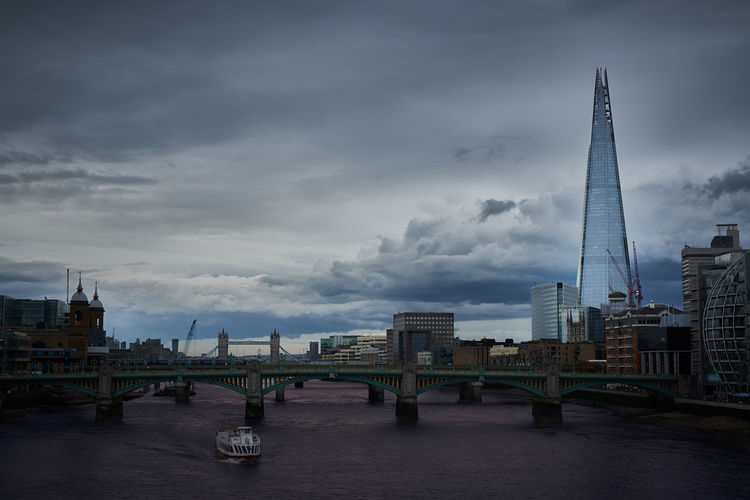 Bridge Over Thames River In City Against Cloudy Sky