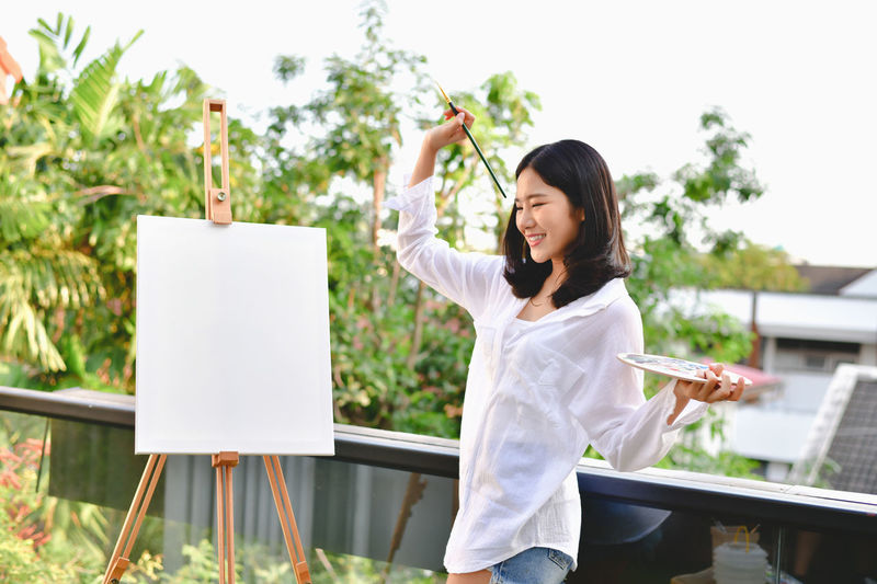 Smiling young woman painting while standing in yard