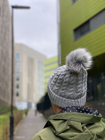 Rear view of woman with umbrella against building in winter