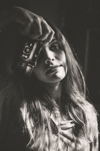 Portrait of young woman holding a vintage camera