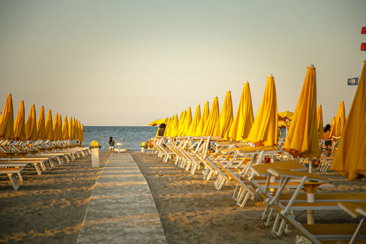 Panoramic shot of deck chairs on beach against clear sky