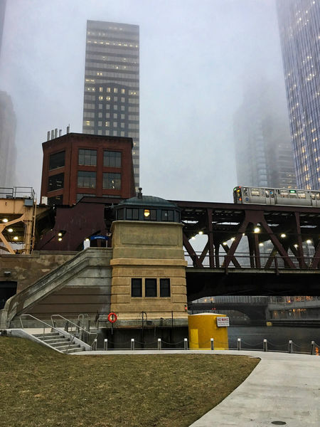 """Foggy day in Chicago Loop as elevated """"el"""" train passes over the Chicago River in winter. Chicago Chicago River Chicago El Chicago Loop Downtown Chicago Elevated Track Life Preserver Stairs Architecture Bannister Bridgehouse Building Exterior Built Structure City Day Elevated Train Foggy Modern No Wake Zone Outdoors Riverwalk Sky Skyscraper Stairwell Travel Destinations"""