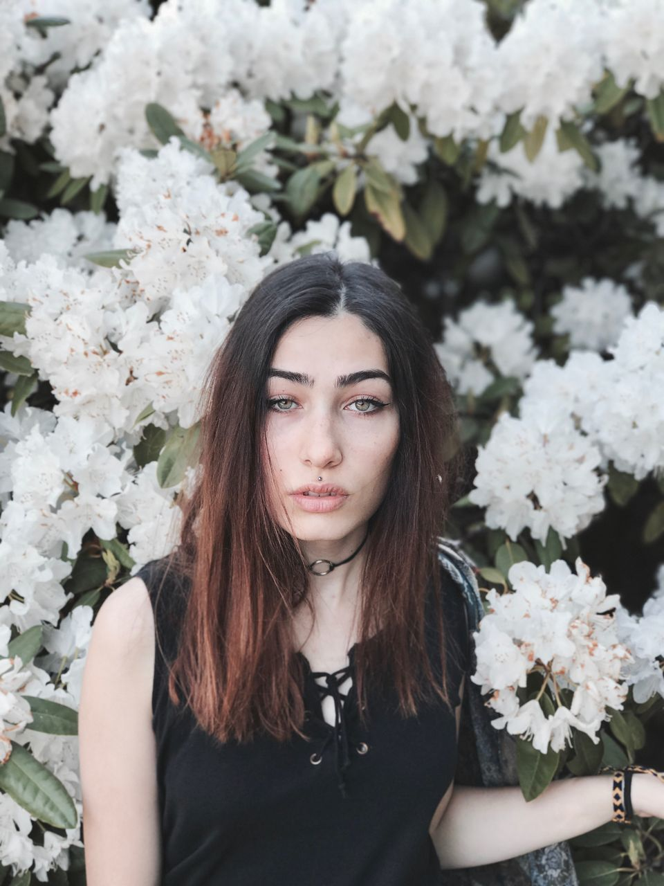 Portrait Of Young Woman Standing Against Flowers