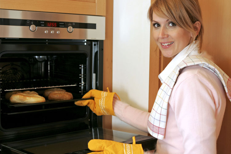 Woman in the kitchen at the oven Oven Woman Appliance Bake Baked Domestic Kitchen Domestic Life Domestic Room Happiness Home House Work Indoors  Kitchen Lifestyles Looking At Camera One Person Oven Portrait Rolls Smiling Women