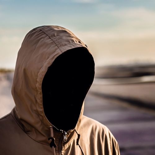 Person in hooded shirt against sky