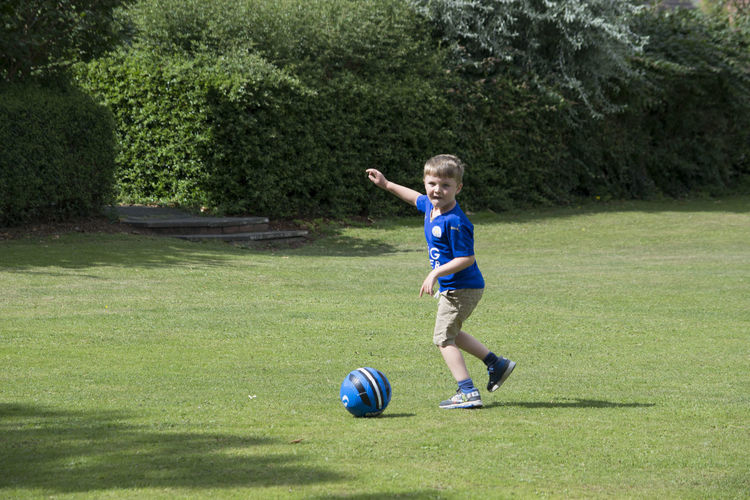 Boy Playing Soccer On Grassy Field