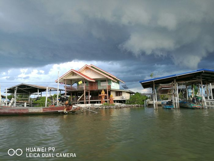 Houses in river against cloudy sky