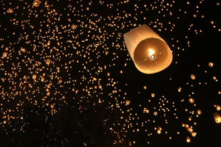 Low angle view of paper lanterns flying in mid-air at night