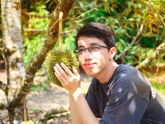 Portrait of young man holding fruit growing on tree