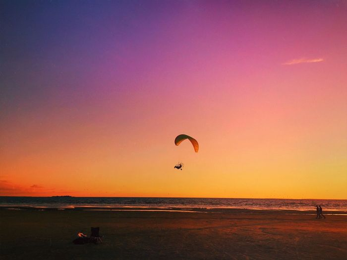 Scenic view of paraglider over sea at sunset