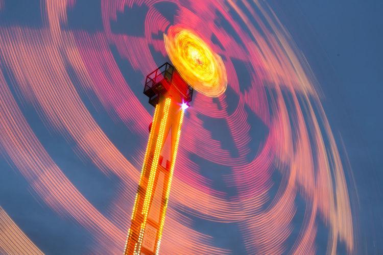 Illuminated ferris wheel light trails against sky
