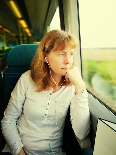 Woman Looking Through Window While Traveling In Train