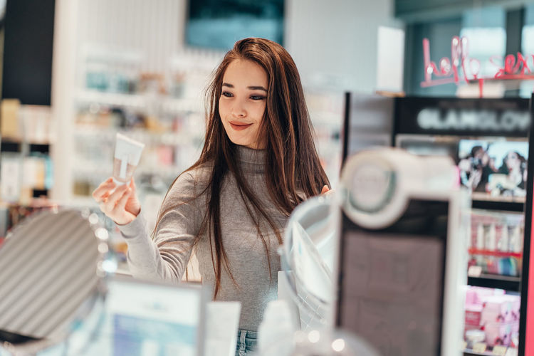 Smiling young woman shopping at cosmetic store