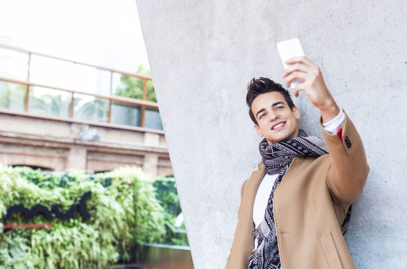 Young man taking selfie from mobile phone by wall