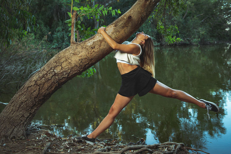Side view of woman sitting on tree trunk in forest