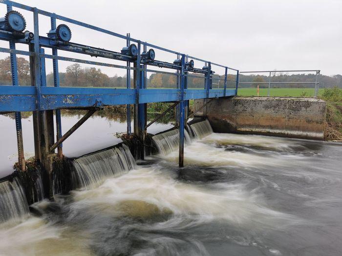 Water flowing in dam against sky