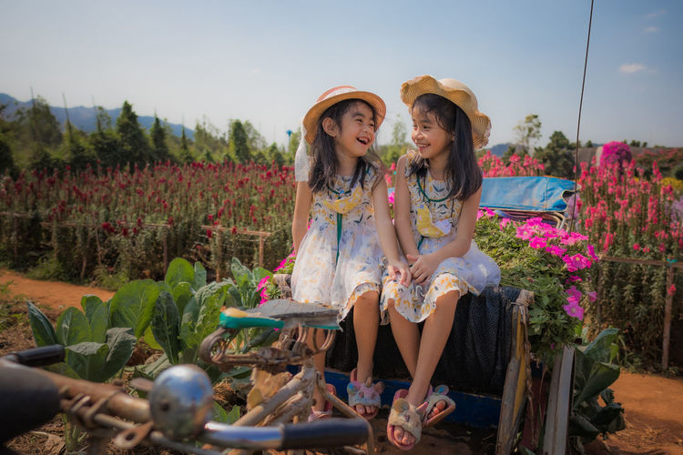 Full length of mother and girl sitting by plants