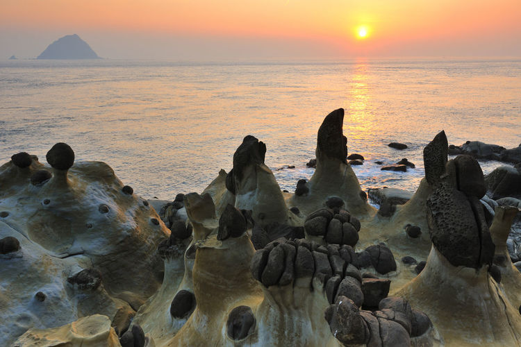 Rock Formations By Sea Against Sky At Sunset
