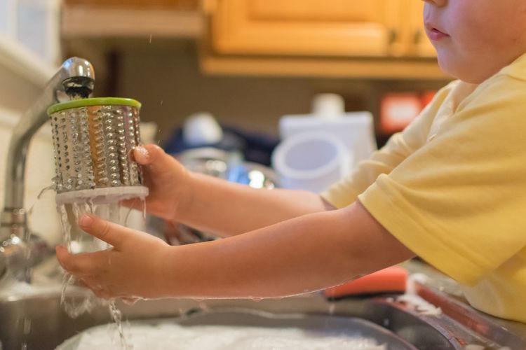 Boy washing container at kitchen sink