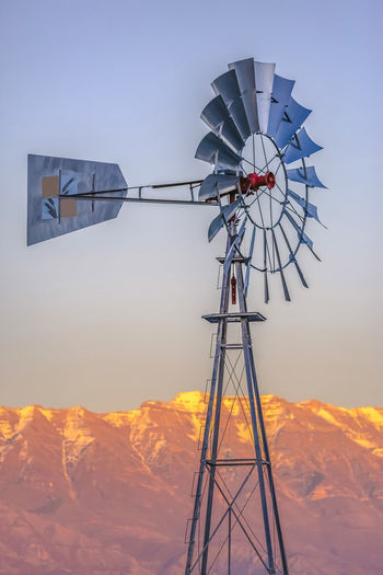 Windmill and mountain against clear sky