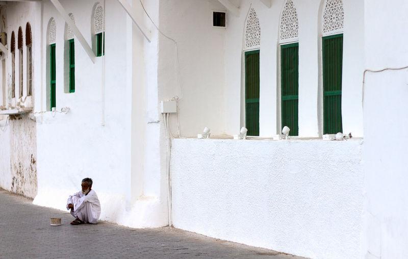 A beggar waits for help, Matrah, Oman Absence Beggar Door Homeless Lifestyles Oman Real People Sitting Wall Window