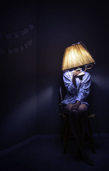 Young woman holding illuminated electric lamp while sitting on chair in darkroom at home
