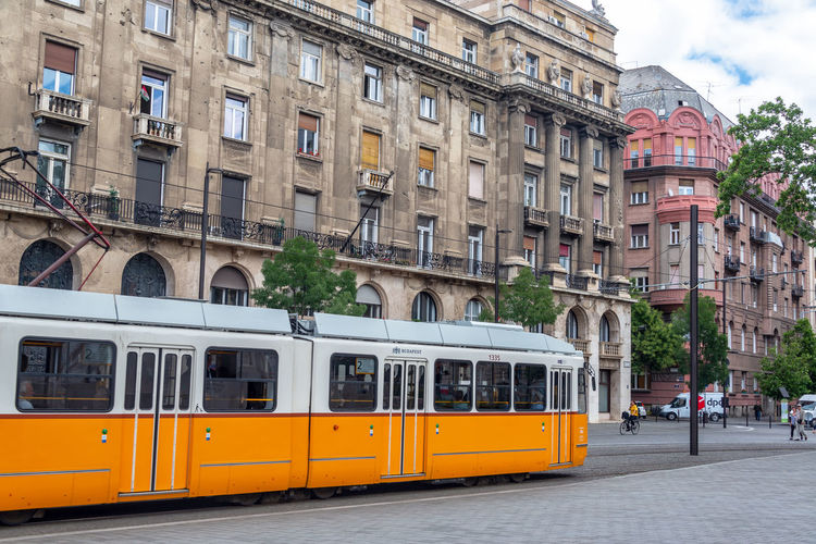 Train on street against buildings in city