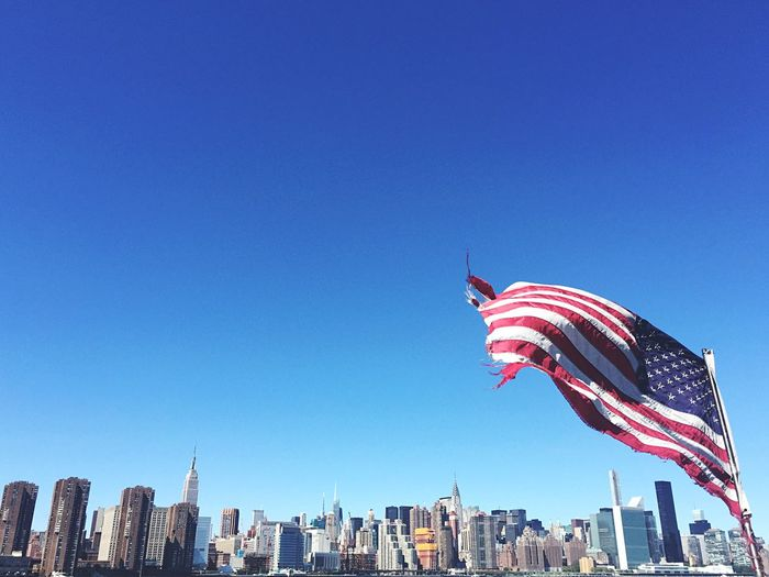 Low angle view of torn american flag blowing against clear sky in city