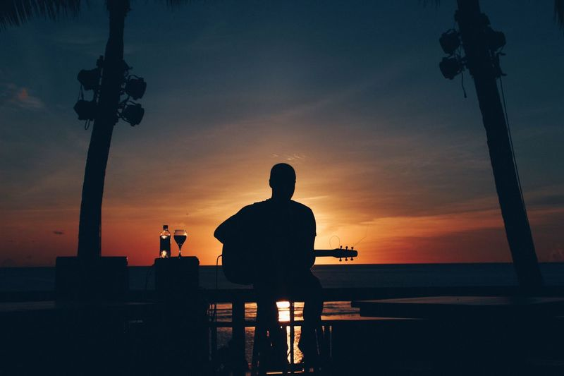 Silhouette man sitting by sea against sky during sunset