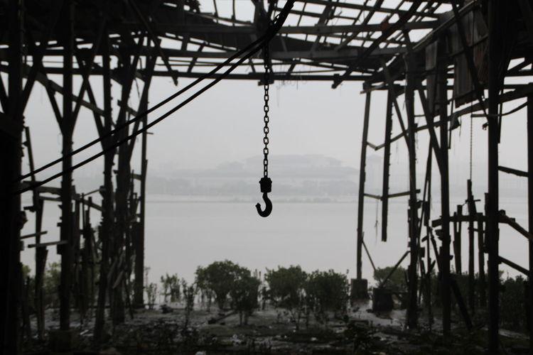 Hook Hanging In Abandoned Building Against Lake