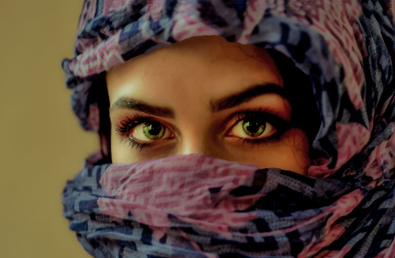 Close-up portrait of young woman covering face with scarf