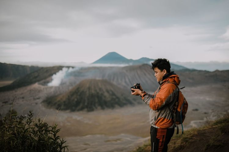 Side View Of Man Photographing Against Mountains