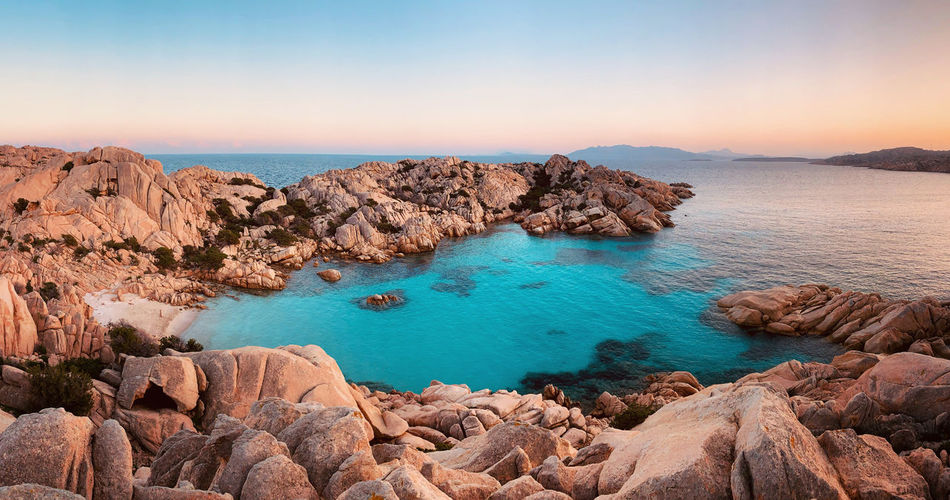 Panoramic view of rocks on sea shore against sky