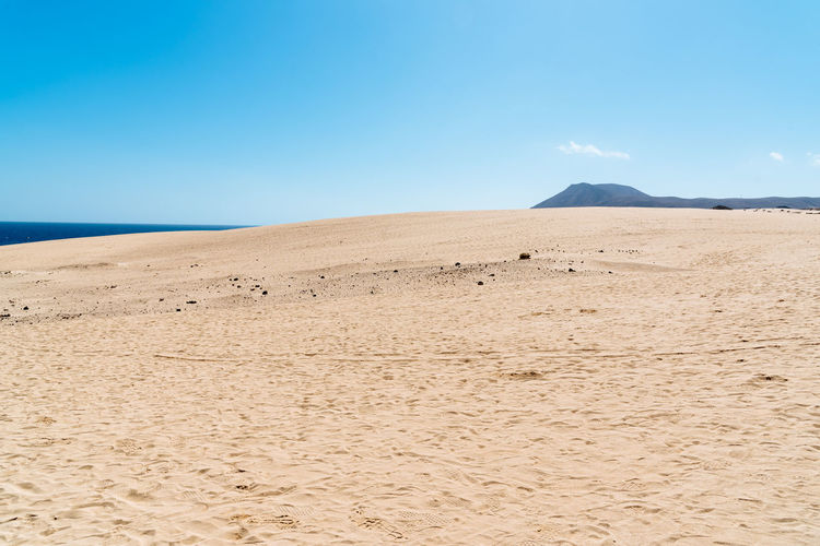 Scenic view of sand dunes against sea and sky Desert Dunes Fuerteventura National Park Arid Climate Beauty In Nature Blue Climate Copy Space Corralejo Desert Environment Land Landscape Mountain Nature No People Outdoors Remote Sand Sand Dunes Scenics - Nature Sky Tranquil Scene Tranquility