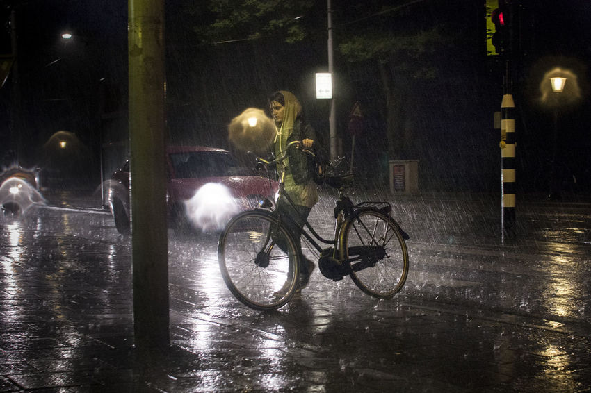Young woman with bike in Amsterdam Amsterdam Bicycle Bike Building Exterior Emotion Illuminated Land Vehicle Mode Of Transport Mood Nature Night One Person Outdoors People Rain Rainfall Rainy Season Real People Streetphotography Transportation Water The Photojournalist - 2017 EyeEm Awards