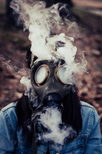 Close-up of woman wearing gas mask with smoke
