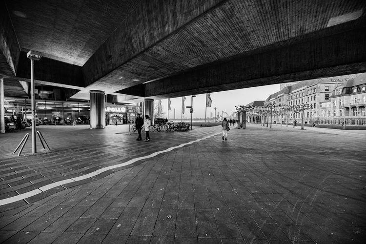 Duesseldorf, Germany - January 20, 2019: Unidentified individuals stroll along famous Apollo theater under a bridge at river Rhine in Duesseldorf B&w Photography Black And White Photography #abstract #clouds #sky #lines #light Architecture Built Structure Group Of People Real People Indoors  Day Incidental People Men Architectural Column Ceiling Transportation People Lifestyles Leisure Activity Women City Travel City Life Nature