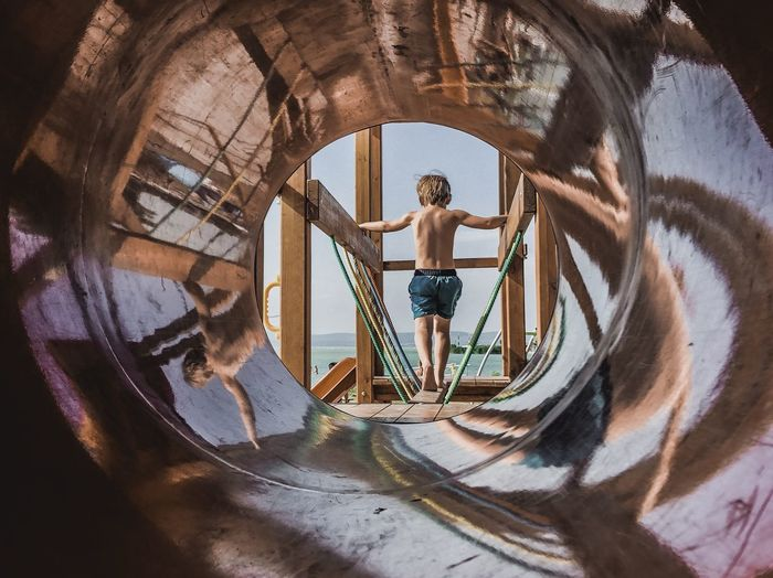 Full length of shirtless boy standing against sea