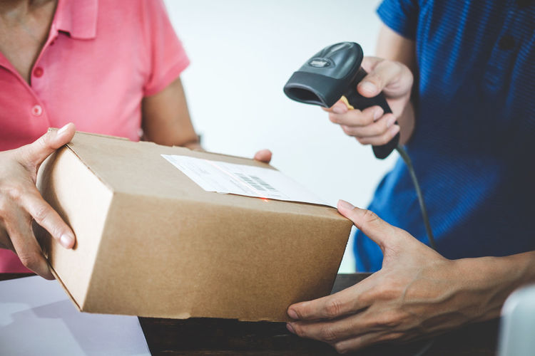 Midsection of male worker scanning barcode on package held by woman