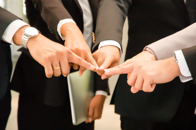 Midsection Of Business People Touching Fingers At Office